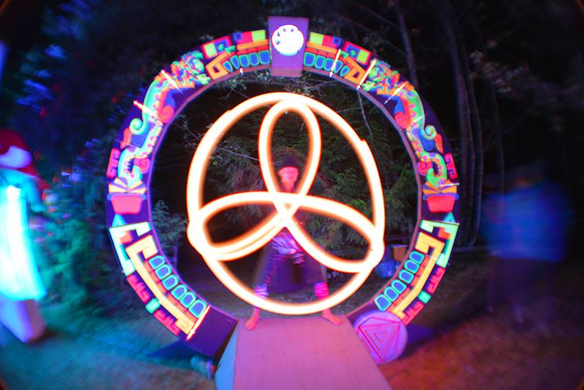 LED poi spinner at night in front of glowing art piece