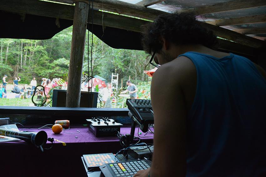 Person in a dj booth looks down at gear while people set up decor outside