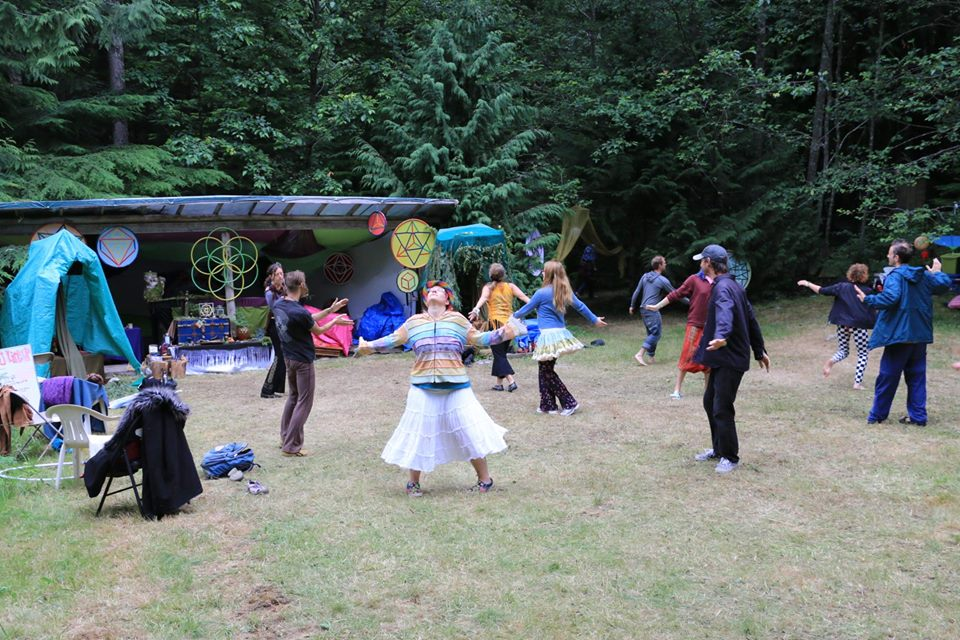 A group of people in a circle on a grassy field doing a movement exercise.  In the background is art, and altar and sound equipment.